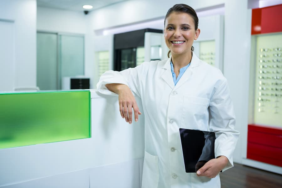 Portrait of smiling optometrist holding digital tablet in optical store