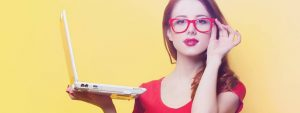 a woman holding a laptop red glasses 1024x384 1
