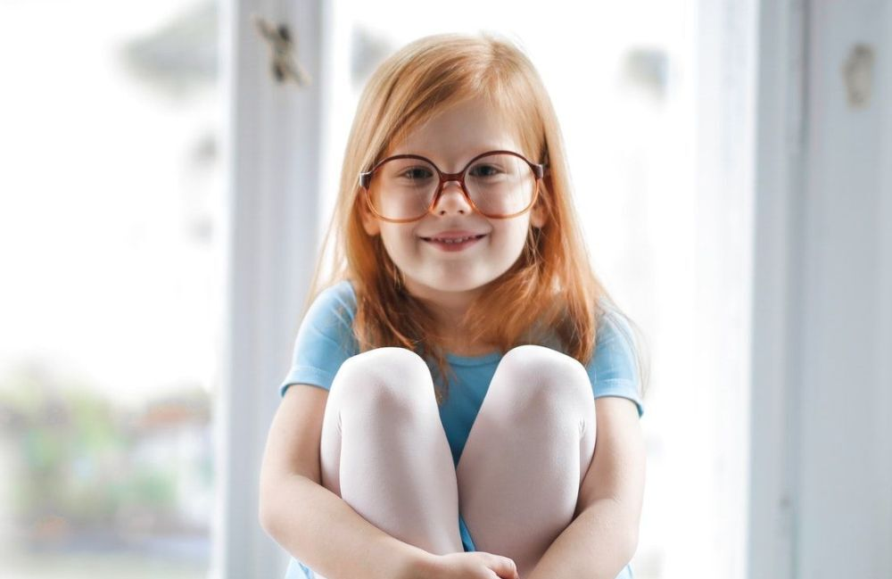 child-girl-redhead-smiling-glasses-blue-ballet-dress-1000px